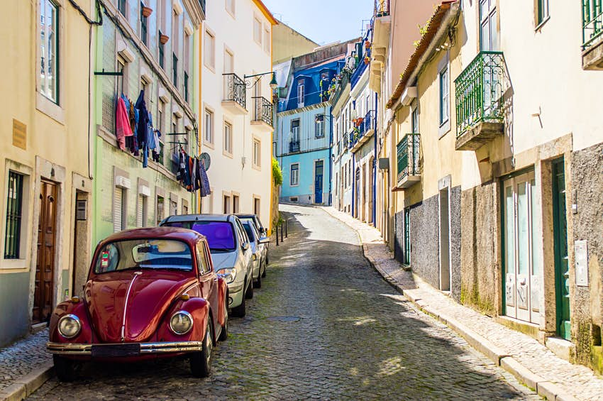 A narrow Portuguese street with old classic vintage VW Beetle car parked in Lisbon, Portugal.