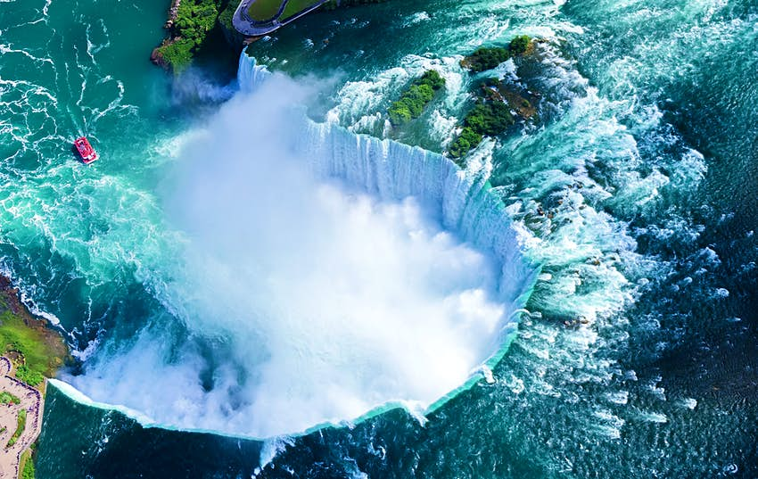 An aerial view shows a horseshoe-shaped waterfall.