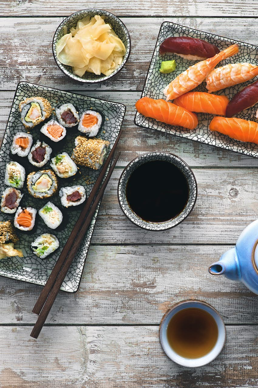 A shot of impeccably prepared Japanese dishes, including fish, sushi, cabbage, soup and tea