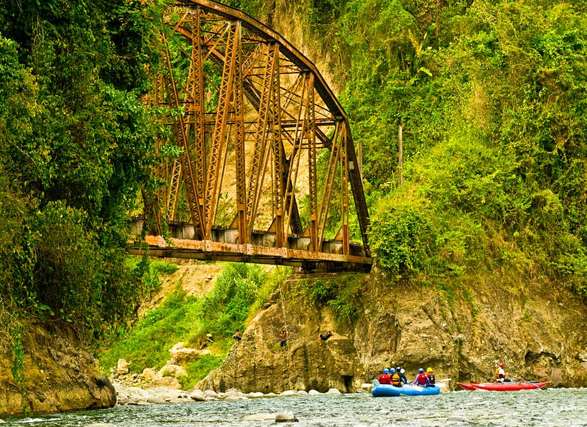 Rafters paddling under an old railroad bridge with kids swinging from a rock, in the Lower Pacuare River.