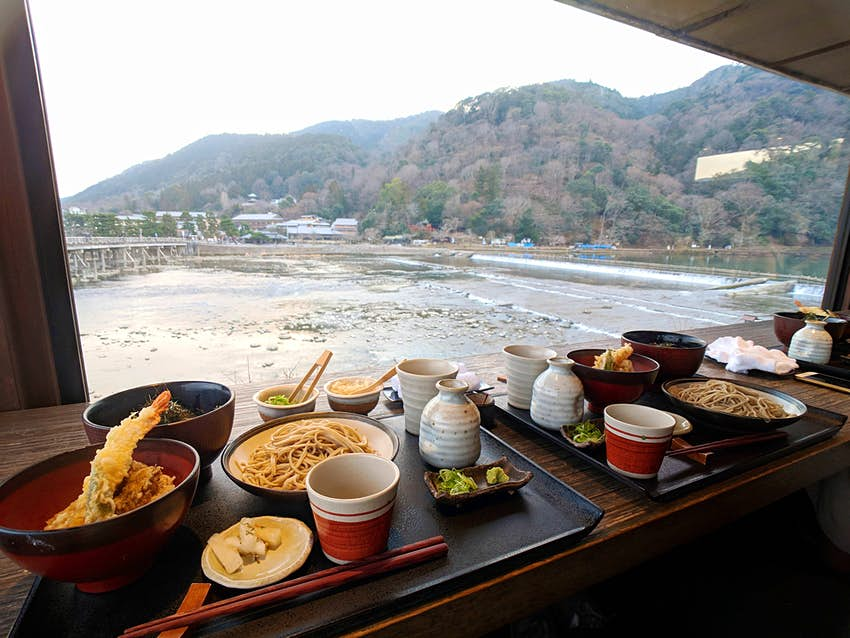 Noodles and deep-friend vegetables make up a meal that is set on trays at a counter looking out over a waterway
