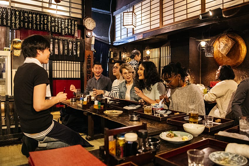 A multiethnic group of friends ordering food at a counter in a Japanese Izakaya