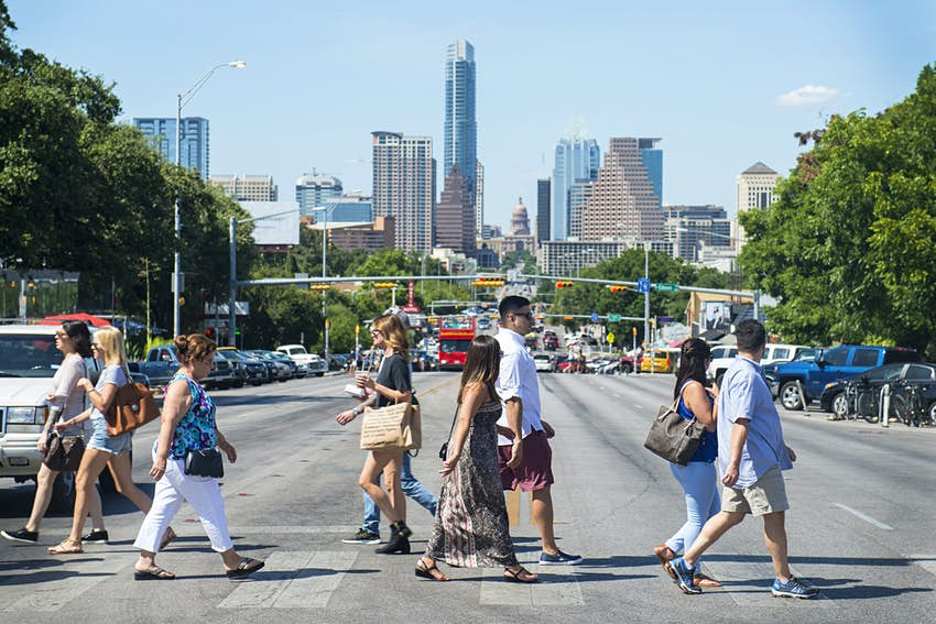 Pedestrians cross South Congress Avenue with the downtown skyline seen in the background in Austin, Texas, U.S., on Saturday, July 23, 2016. Consumer confidence was little changed in July as Americans remained positive about the job market and the business environment, according to a report from the New York-based Conference Board on Tuesday. Photographer: Matthew Busch/Bloomberg via Getty Images