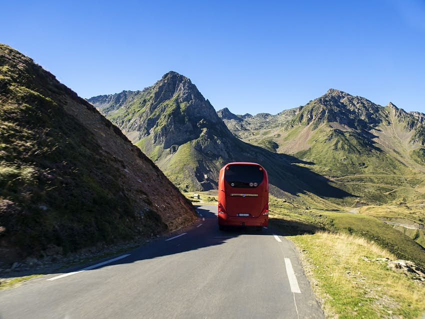 The back of an orange coach heading downhill in a remote mountainous area