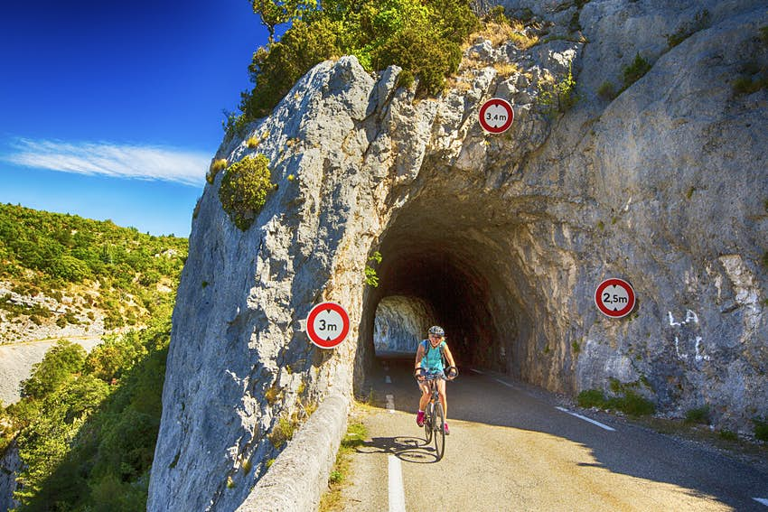 A cyclist rides through a narrow tunnel cutting through the centre of a large cliff