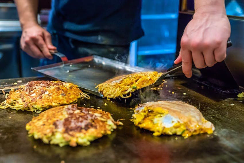 A chef cooking a cabbage and egg-based pancake on a hot plate