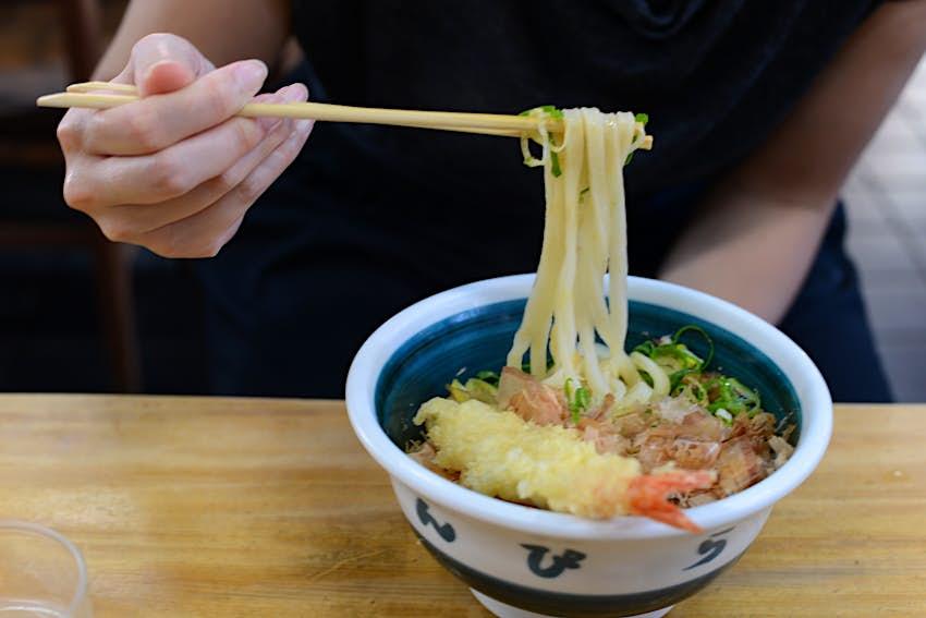 Chopsticks lifting noodles above a bowl