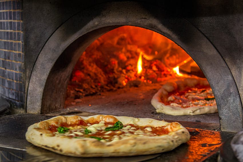 Pizza entering a wood-fired oven in Naples