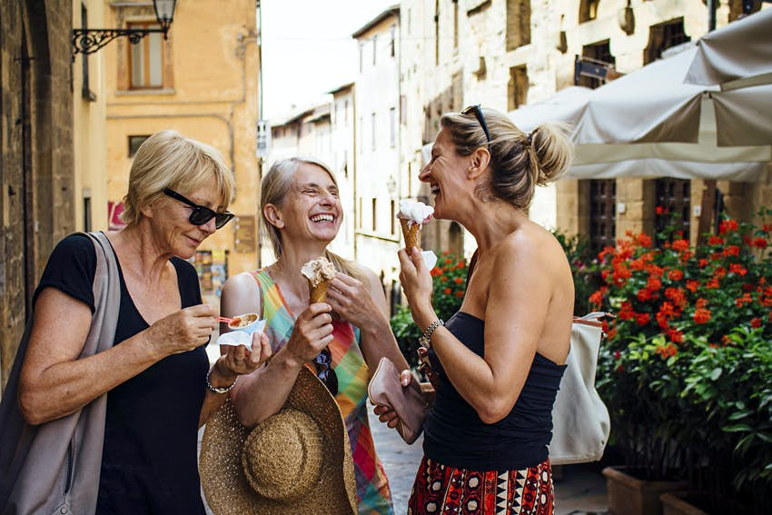 A group of three female friends eating ice cream on an Italian street