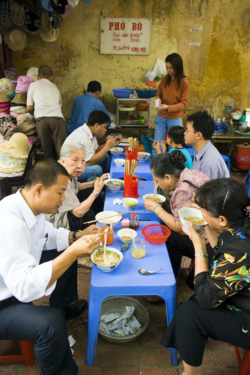 People dining at street food stall, Old Quarter, Hanoi.