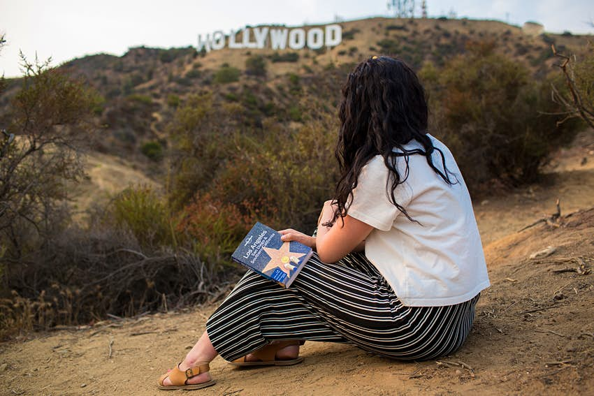 Woman holding LP Los Angeles, San Diego and Southern California guidebook with Hollywood sign in background.