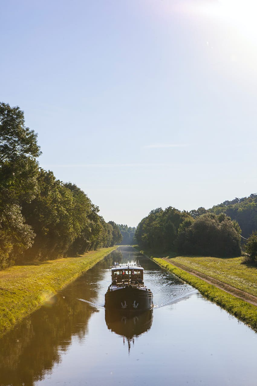 A houseboat traveling down a straight channel with grassy banks