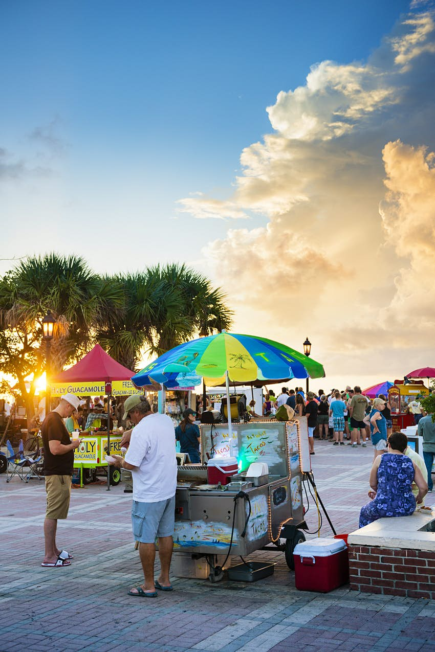 Food carts and performers entertain visitors to Mallory Square Dock at sunset