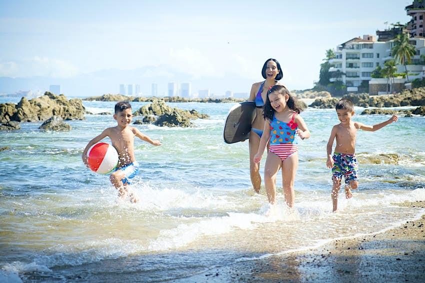 México, Puerto Vallarta, madre y tres hijos divirtiéndose en el paseo marítimo