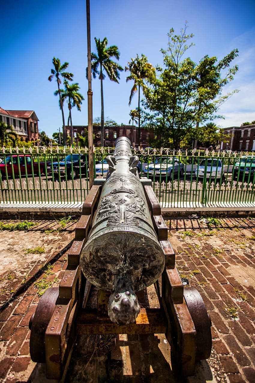 An old ornate cannon sits on a brick sidewalk facing an old building in Spanish Town Jamaica