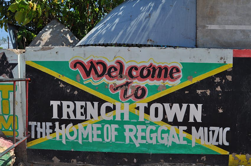 """Concrete wall with the words """"Trench Town The Home of Reggae Muzic"""" painted on top of a painting of the Jamaica green, black and gold flag."""