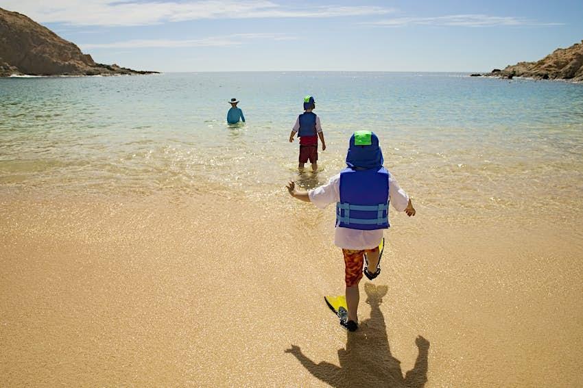 Padre e hijos jugando en la playa de Cabo San Lucas, México