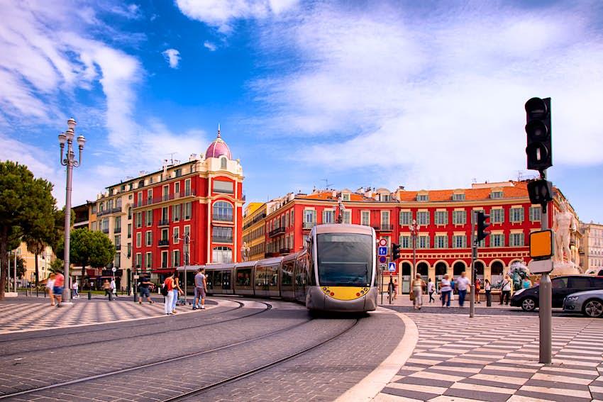 A tram traveling through a pedestrianized area of a city