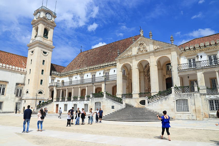 People take photos in front of Coimbra University, a huge white building with an accompanying square. The building also has several large columns near its entrance and a tall clock tower.