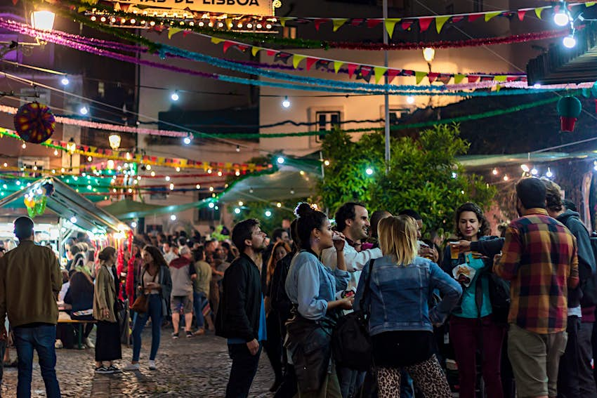 People gathered in a Lisbon street at night during the Saints Festival.