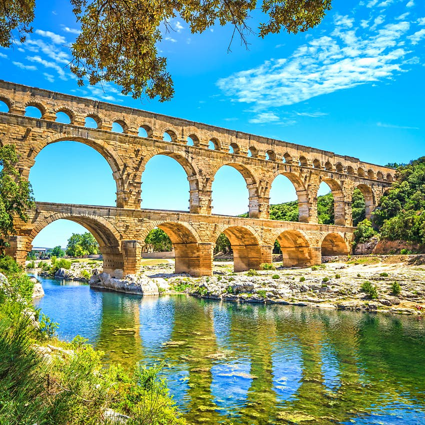 A massive multi-levelled aqueduct with many arches stretching over a river