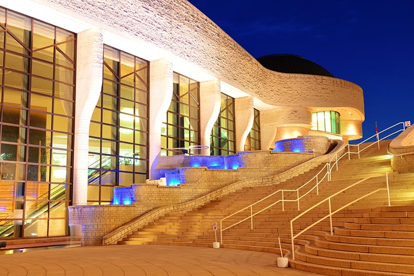 Steps in front of a brightly lit museum building at night.