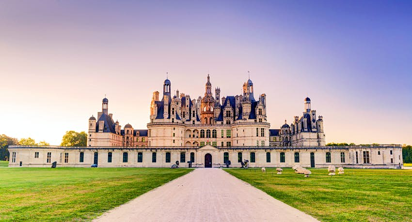 A pathway leading to a vast chateau building with huge turrets