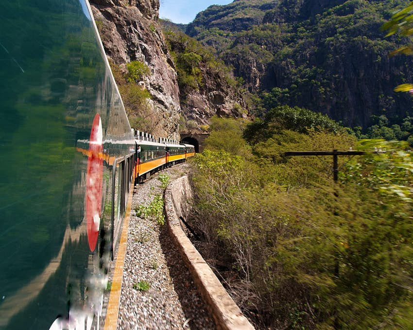 View of the side of train carriages winding their way along the Copper Canyon Railway