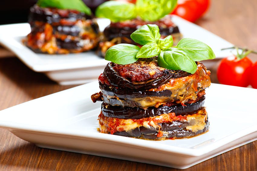 A stack of baked eggplants with cheese oozing between each slice