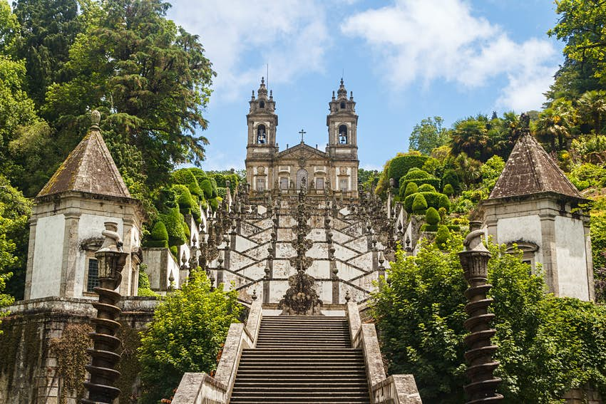 A view of the zigzag stairway leading up to the Bom Jesus church in Braga, Portugal. The church is white, with two towers at either end.