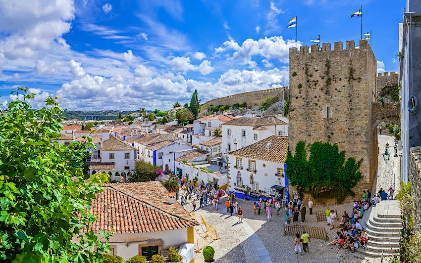 An aerial view of the medieval houses, wall and tower of Obidos, Portugal. The street is filled with crowds of people.