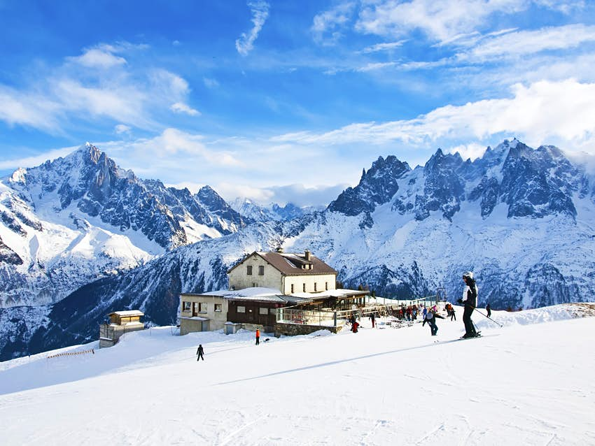 The winter view on the mountains and ski lift station in the French Alps. There ae several skiers on the slopes