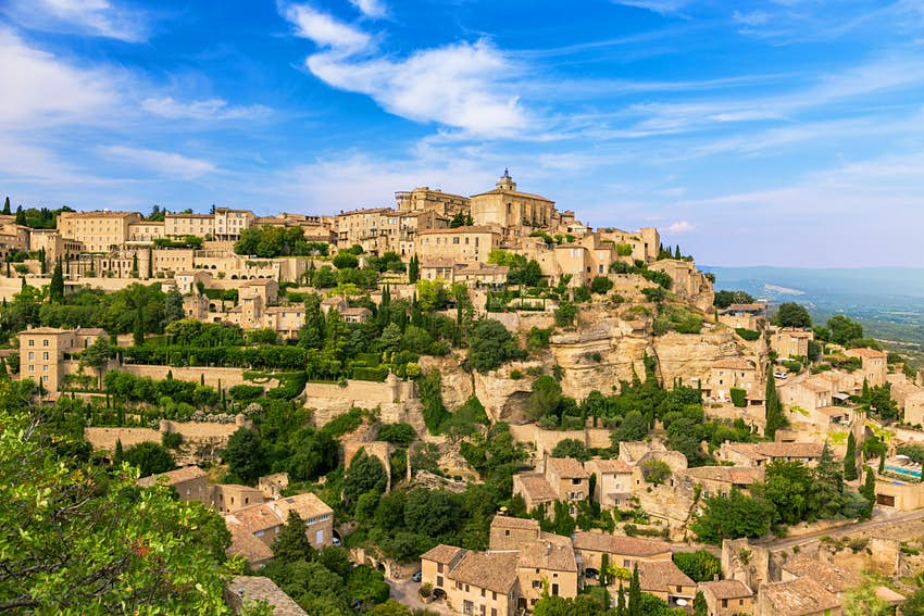 A hillside covered with golden medieval buildings tightly packed together