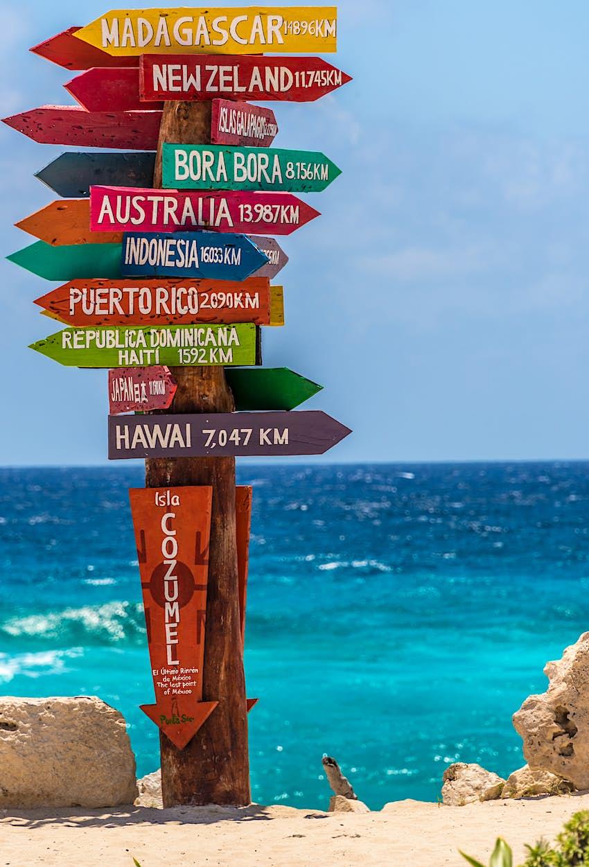 Un cartel colorido cerca de una playa muestra diferentes flechas y distancias alrededor del mundo.