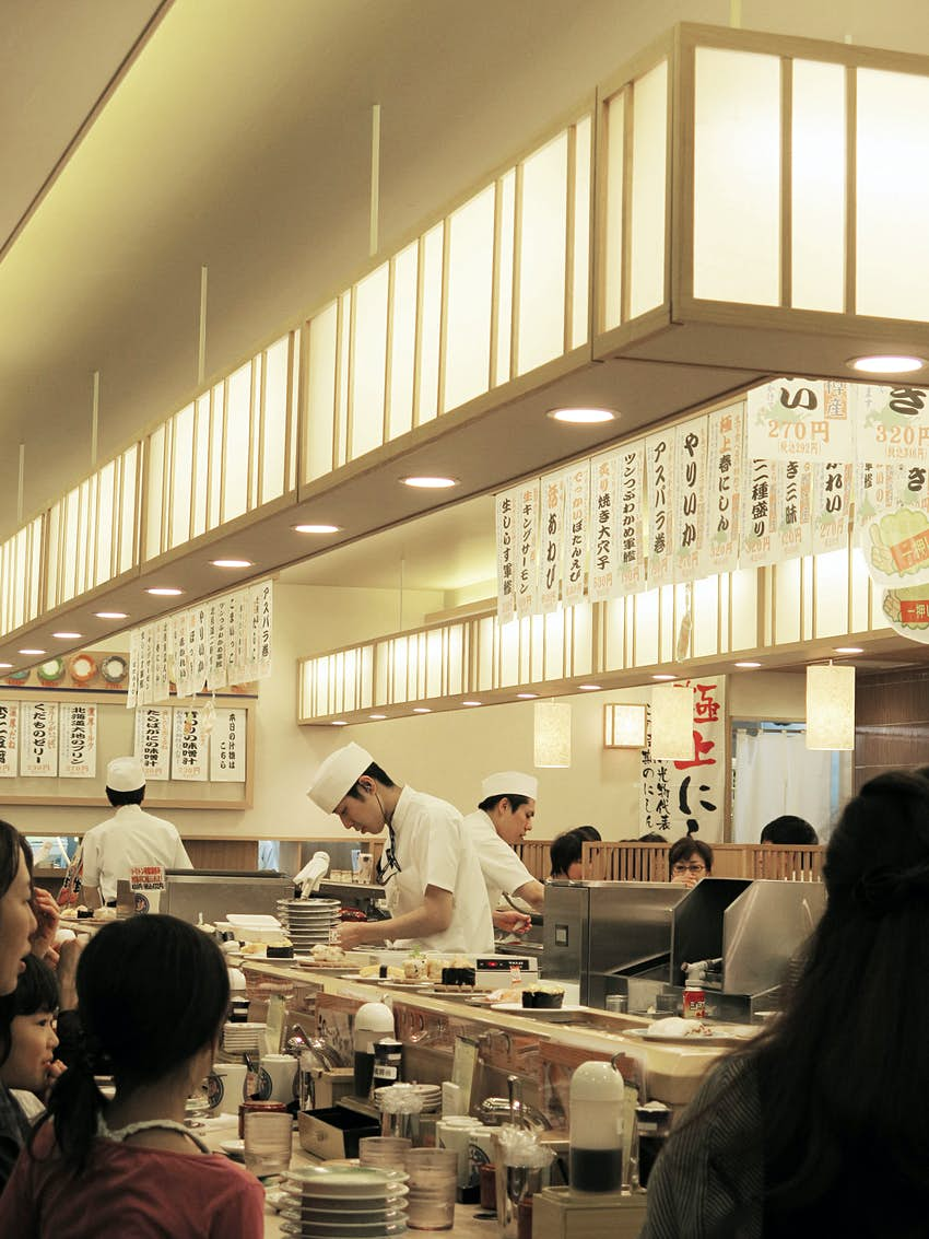 Chefs in white clothes with chef hats work away in a central kitchen. Diners sit at counters around the outside