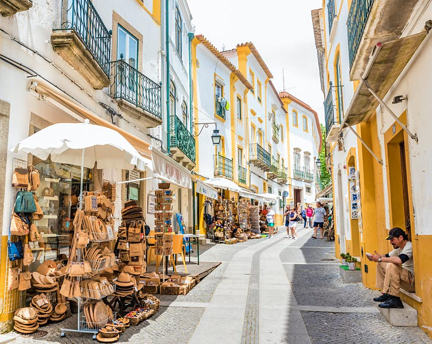 Street view of the Historic Centre of Evora, Portugal. The street is narrow and lined by stalls, selling their wares outside.