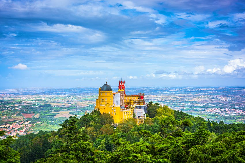 The grand, yellow-walled Pena National Palace stands on a hilltop in Sintra, Portugal. The palace is surrounded by forest.