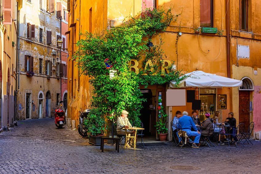 A quiet alley in Rome with people sitting at tables in a corner bar