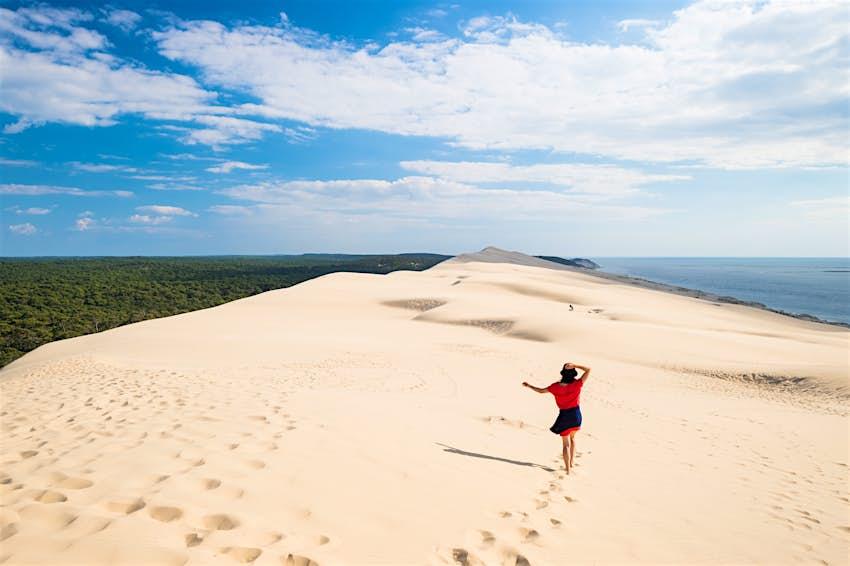 A woman walks along the top of a huge white sand dune near the coast