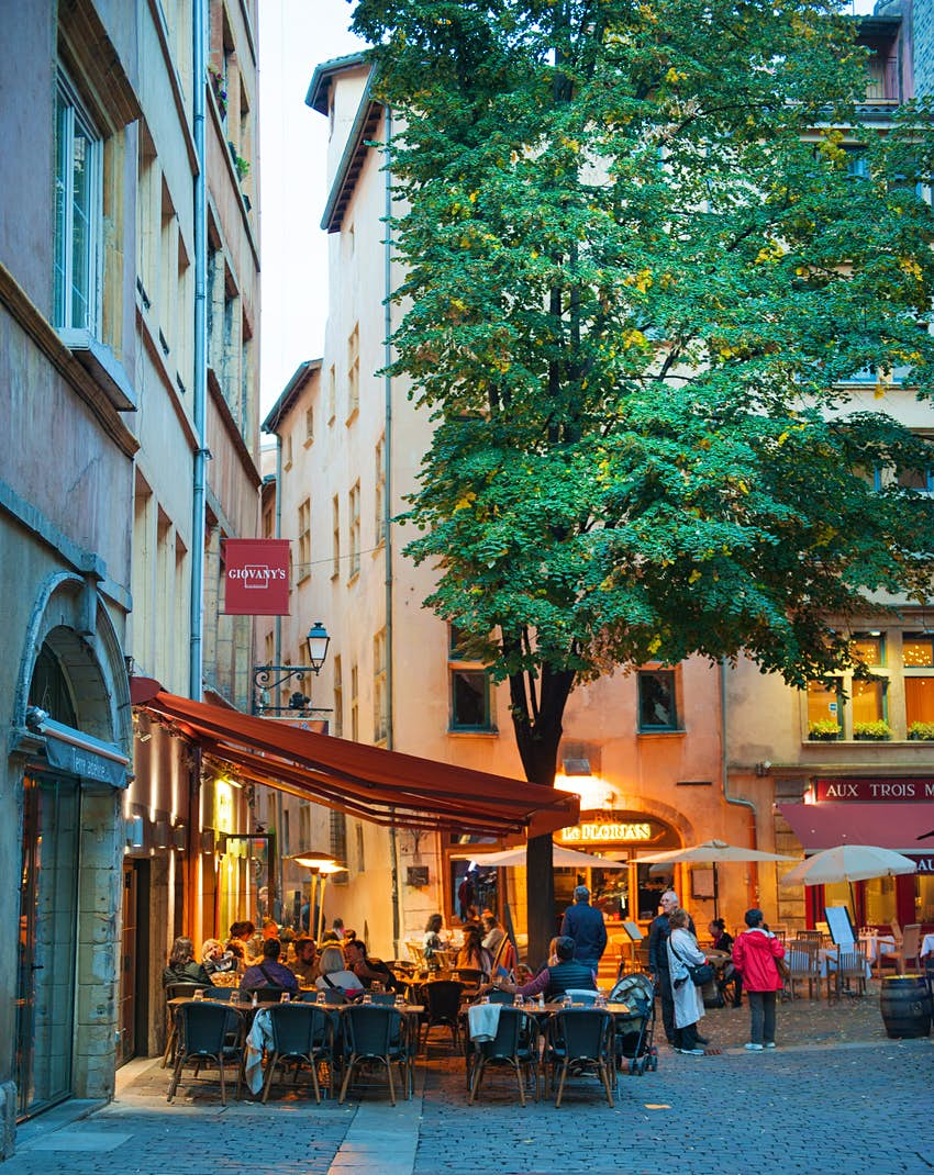 Exterior shot of a small restaurant with a red awning in a cobbled square.