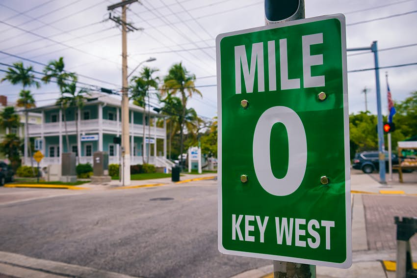 """A street sign reading """"Mile 0 Key West"""""""