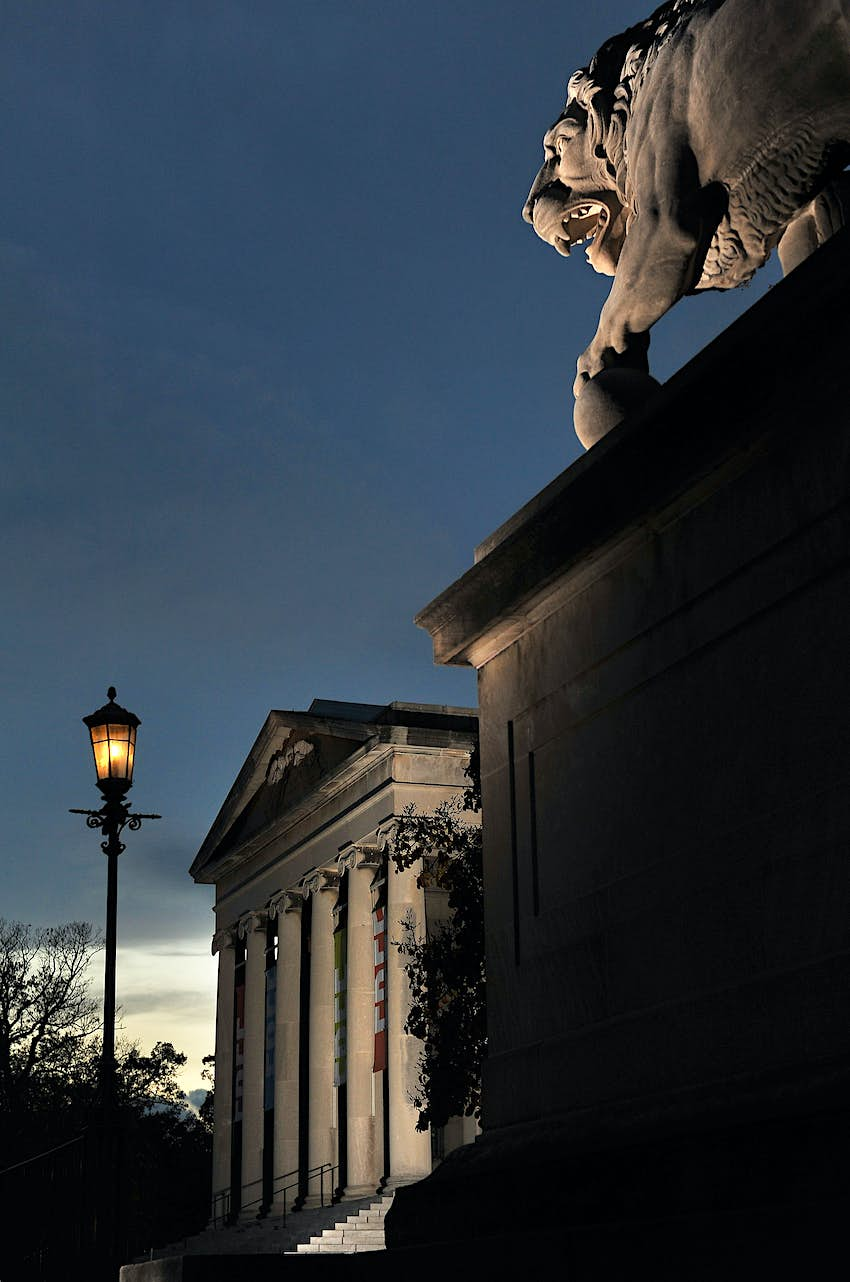 Exterior view of The Baltimore Museum of Art at night. There is a large gargoyle on the roof of the building
