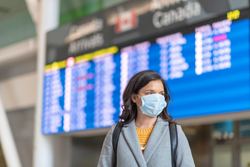 A solo passenger flight has been canceled.  She is standing in front of the departures panel.  She wears a protective mask