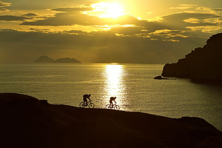 Two mountain bikers cycling on a rocky coast on the island of Crete, Greece.  The sunset behind them means that only the silhouettes of the two cyclists are visible.
