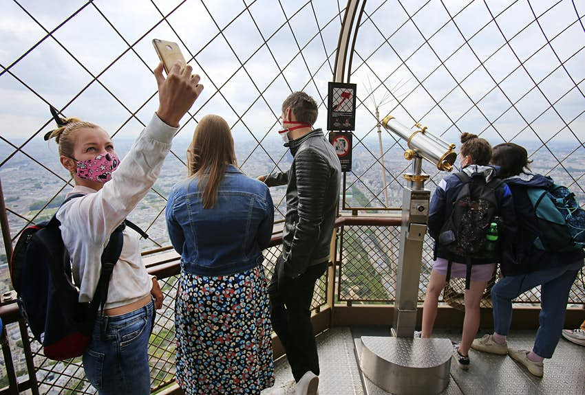 Tourists in face masks on the last floor of the Eiffel Tower