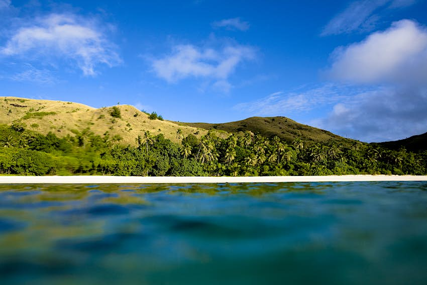 A view of the small island of Nacula, Fiji, from the water. The camera is just above the water level, meaning only a section of the white beach, lush forest and rolling hills of the island are visible.