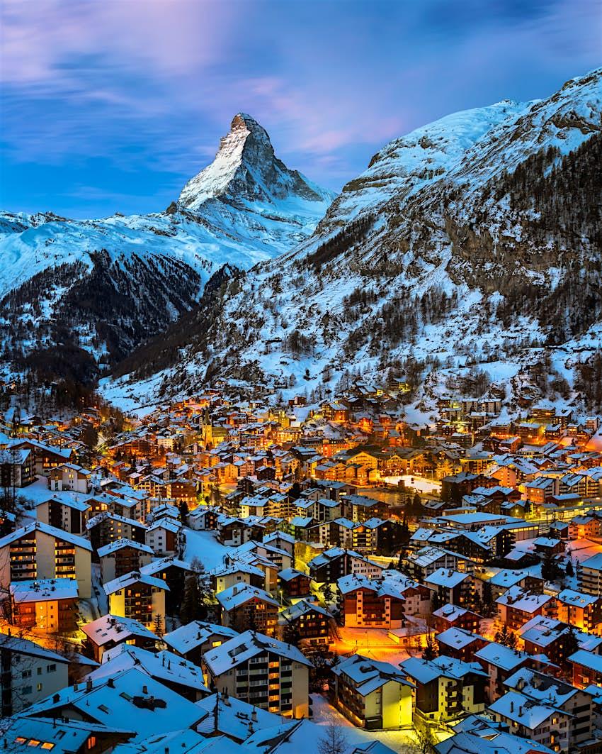 Luftbild des Zermatter Tals in Richtung Matterhorn.  Die Stadt hat viele Gebäude, in denen Lichter in den Fenstern sichtbar sind.  Der Gipfel des Matterhorns ist zerklüftet und mit Schnee bedeckt.