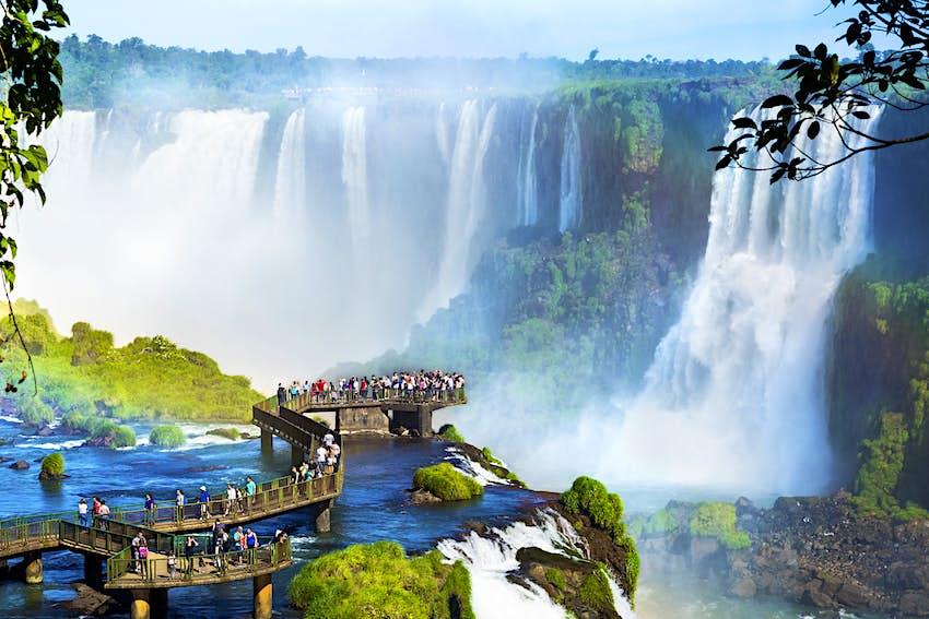 Una serie de impresionantes cascadas se hundieron en un estanque.  Los turistas los admiran desde un malecón.