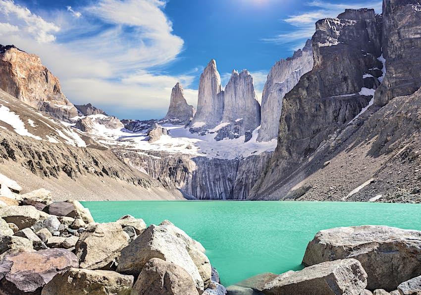Một hồ nước trong xanh rực rỡ được bao quanh bởi các đỉnh xám của dãy núi Torres del Paine ở Patagonia, Chile.