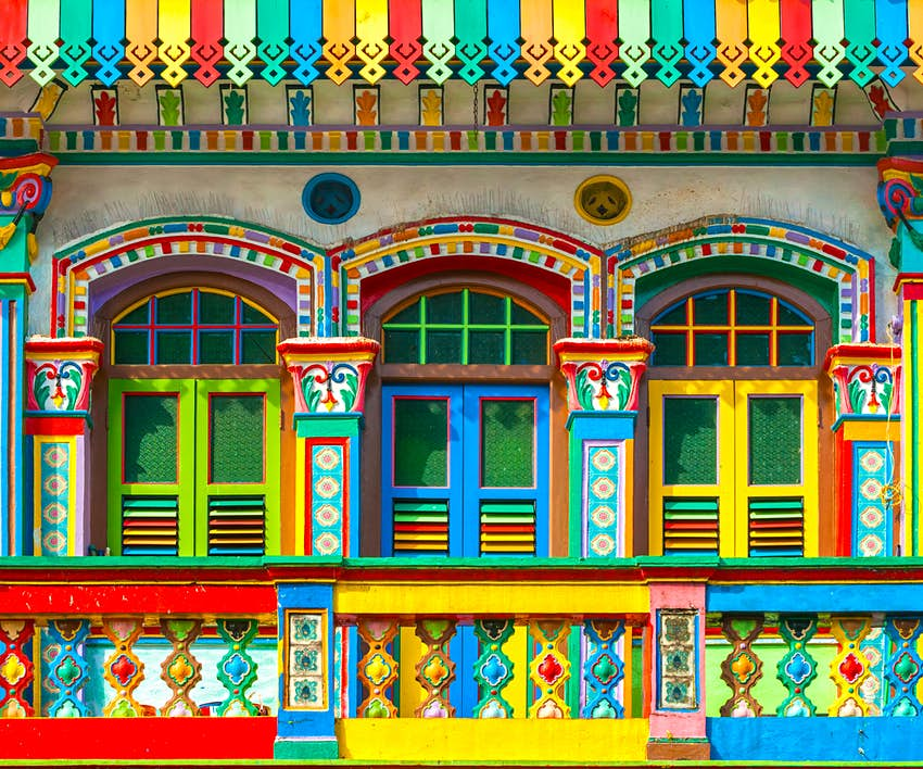 Three colorful Little India shopfronts painted in blues, greens, yellows and reds in Singapore